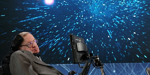 Stephen Hawking sitting against a space screen