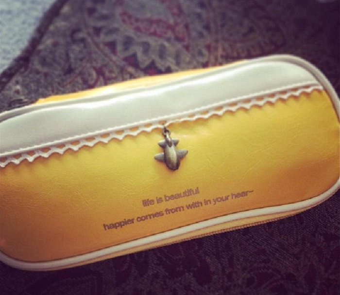 a pencil case with happier comes from with in your hear written on it