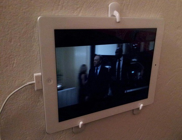 A tablet held by hooks on the wall