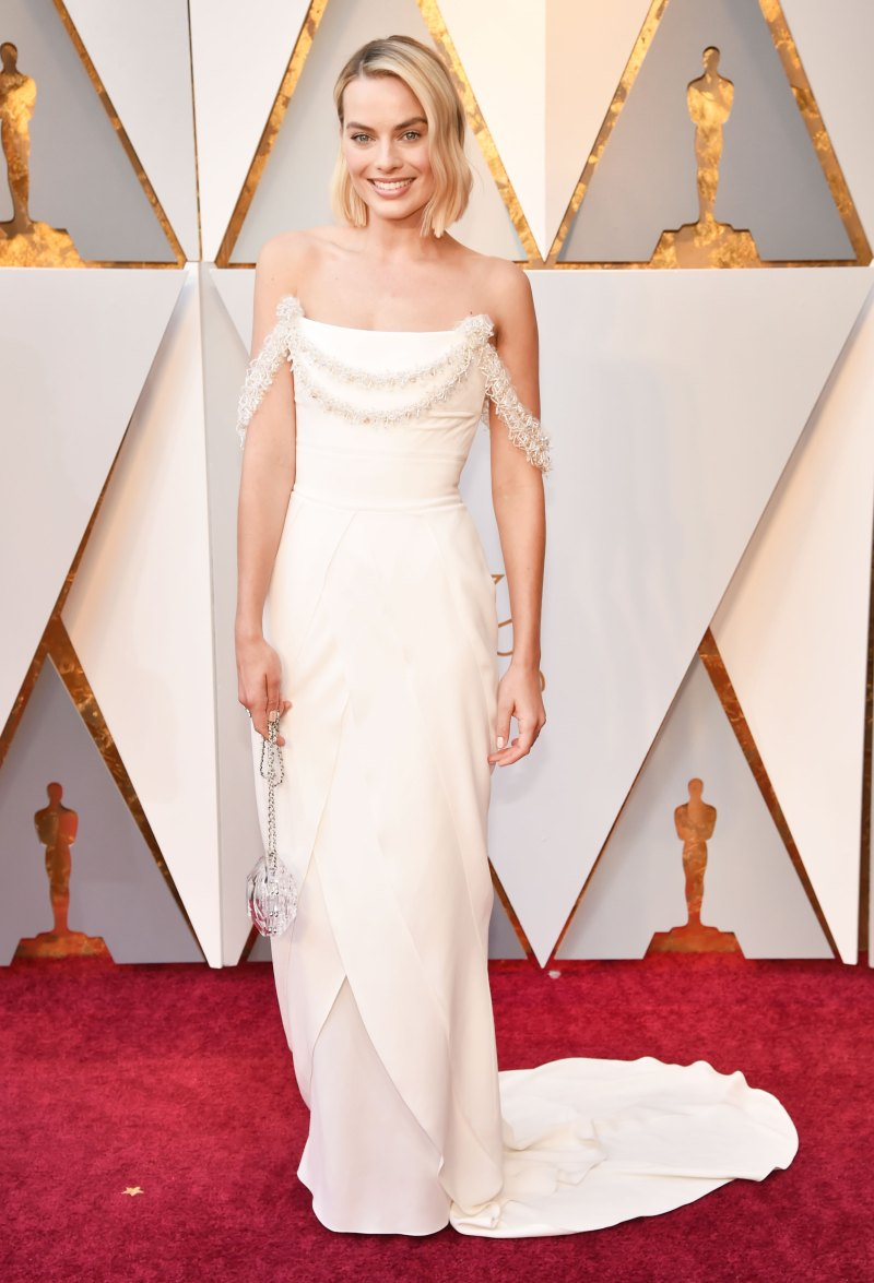 Margot Robbie In a white Chanel gown with beading at the bodice and delicate draping at the shoulders.