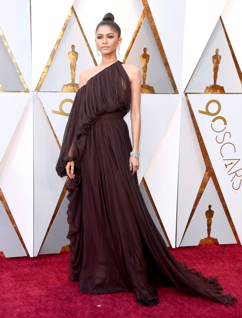 Zendaya Wear a deep burgundy asymmetrical-sleeved Giambattista Valli Couture gown, Brian Atwood sandals and Bulgari jewels.