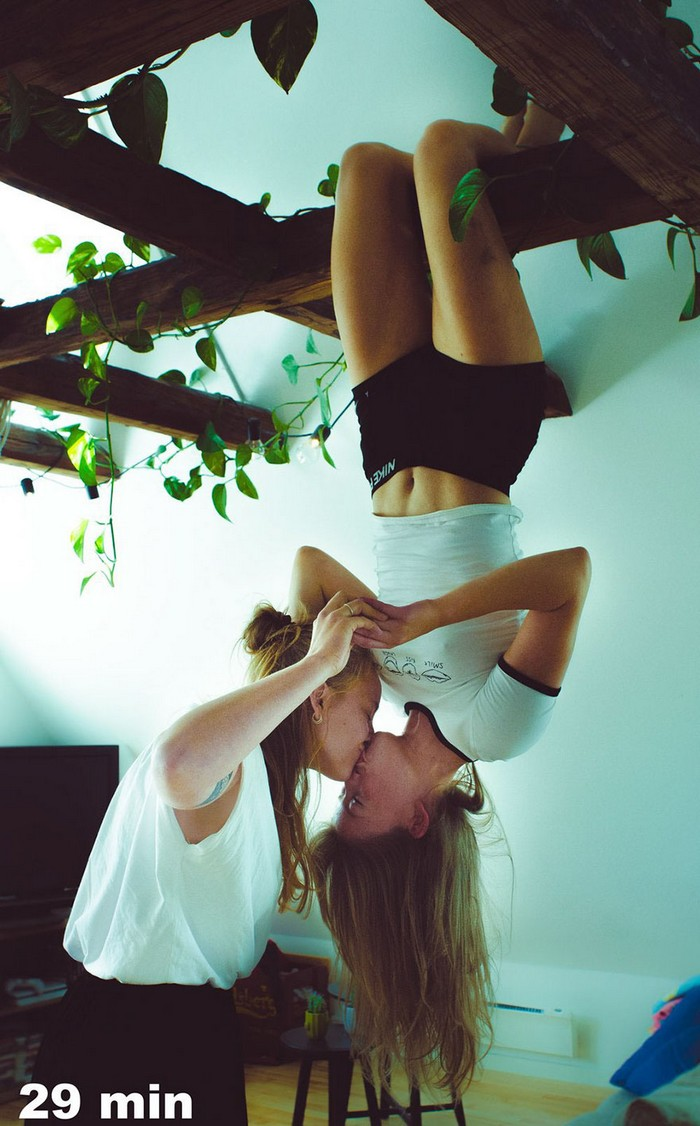 Marie hanging from a wooden beam kissing a woman