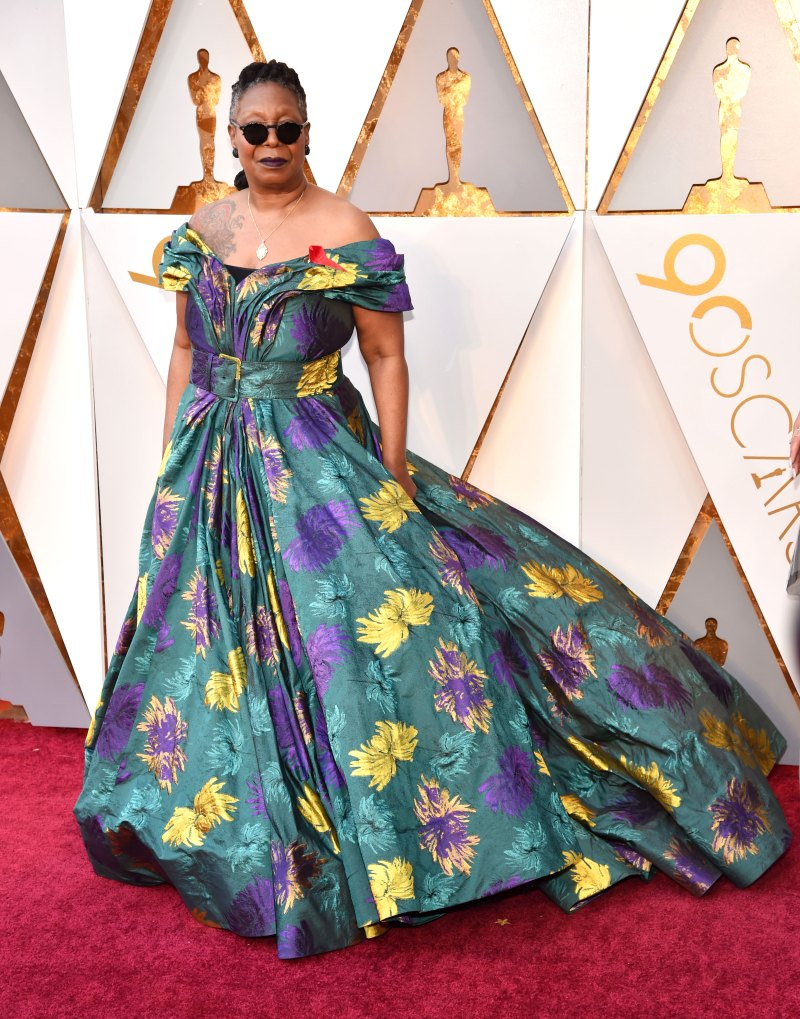 Whoopi Goldberg Wearing a colorful emerald floral gown with an off-the-shoulder neckline and a full skirt.