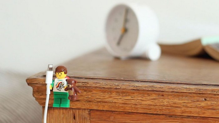 a lego man holding a phone cable